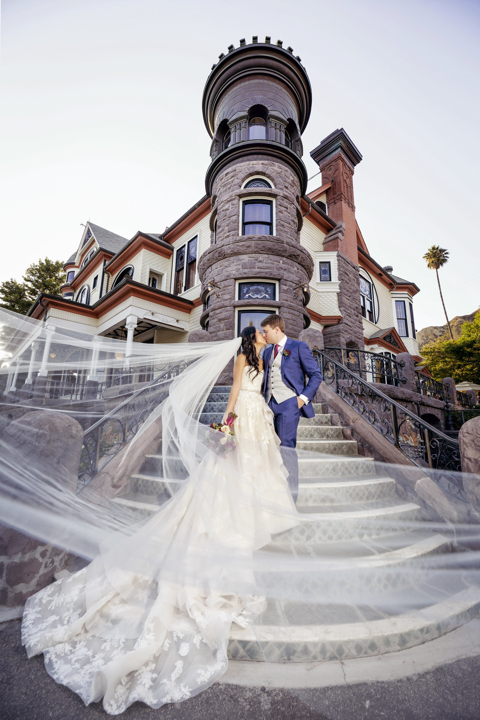 wedding veil shot of bride and groom on front stairs to newhall mansion