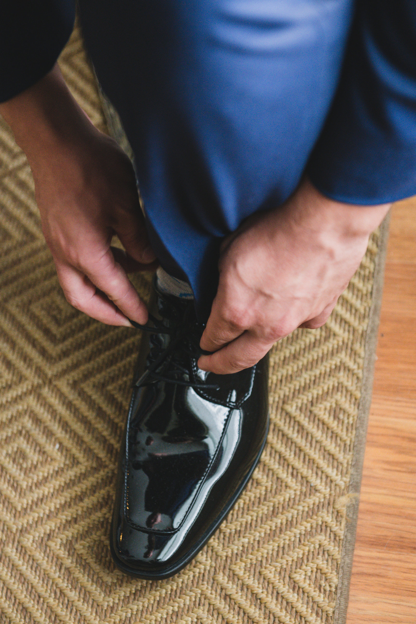 photo of groom tying his shoe laces from wedding at Three Village Inn