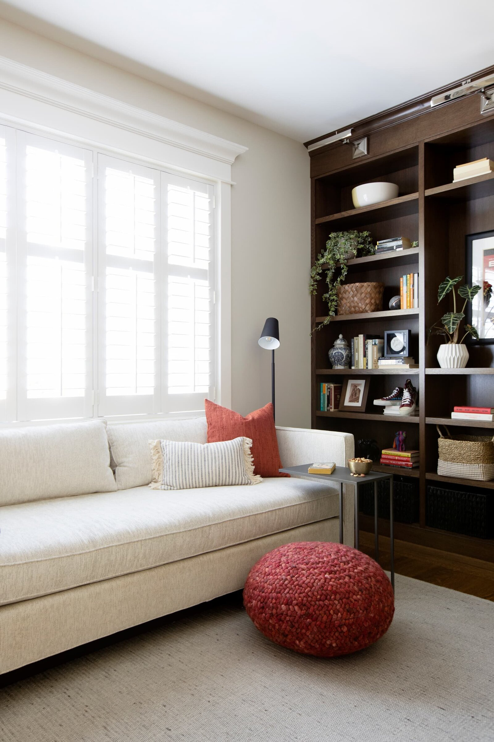 Granville Project l Den-Reading Room l Neutral Sofa with Red Pouf and Black Reading Lamp