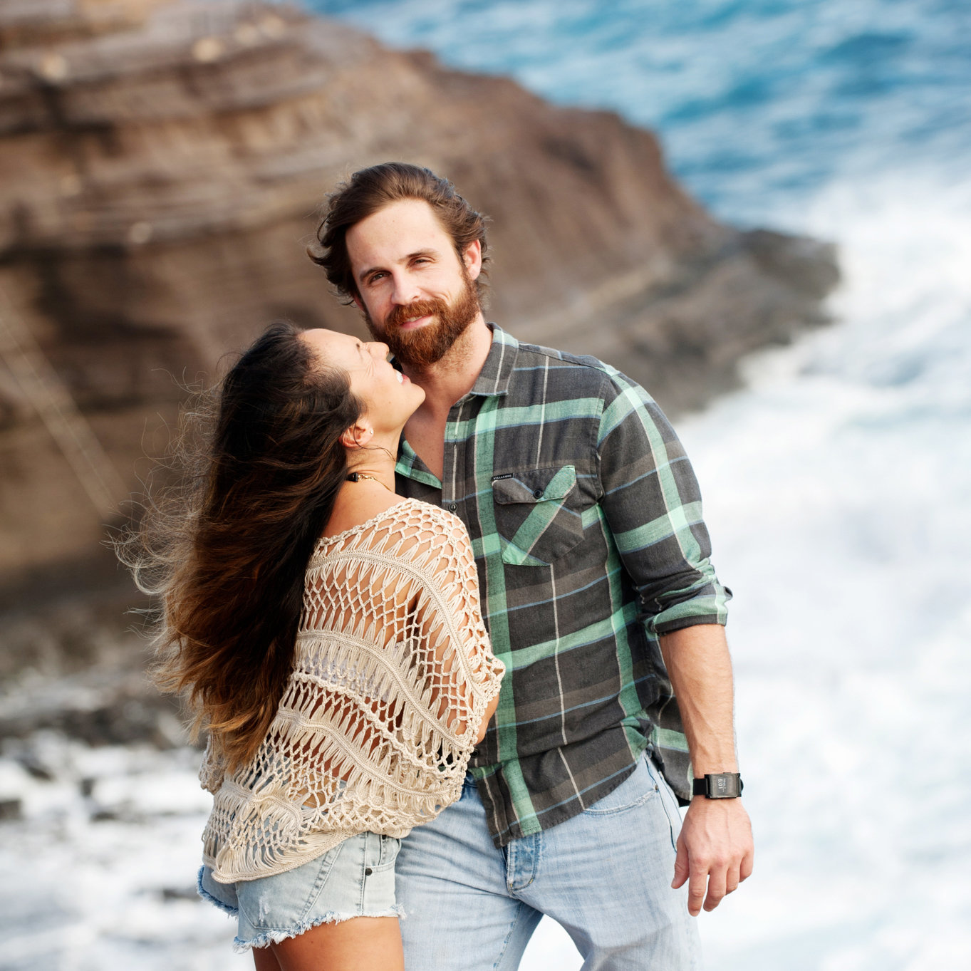 a handsome man looks at the camera as a woman reaches up to give him a kiss with spitting caves hawaii in the background