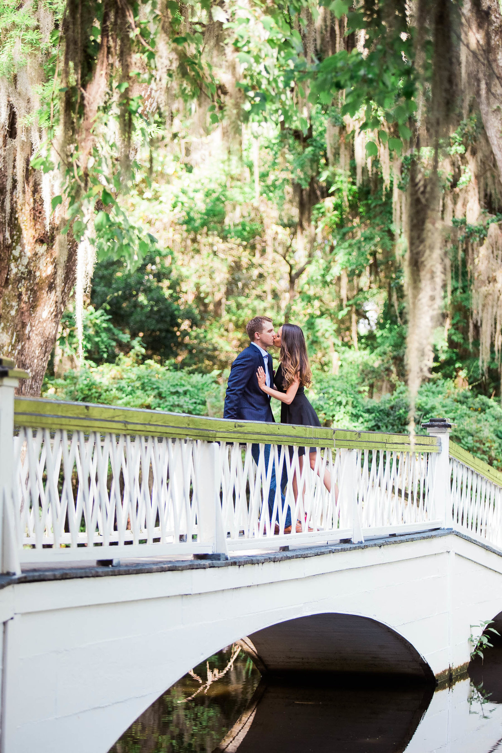 Engaged couple stand on a white bridge, Magnolia Plantation, Charleston, South Carolina