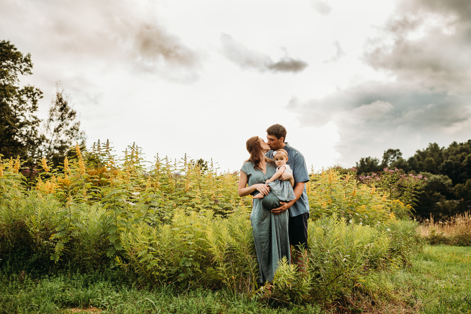 pregnant mother holds daughter and snuggles husband in field in southborough ma