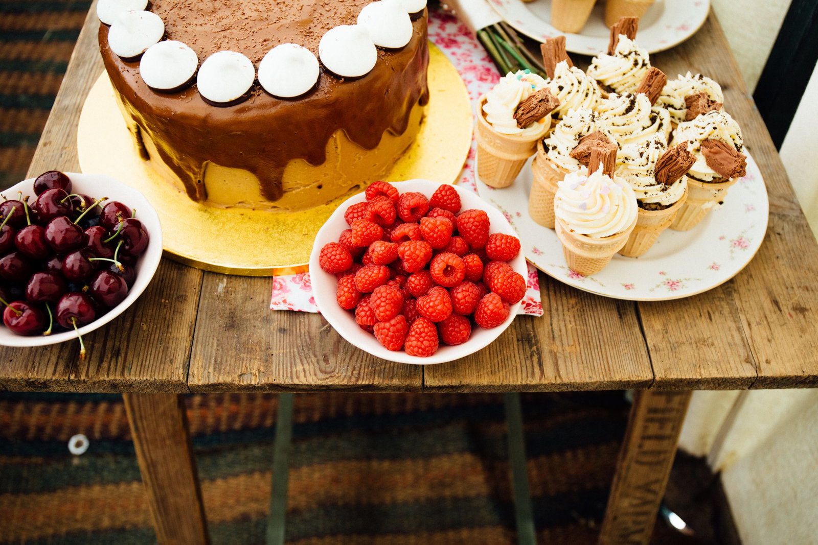 Creative photograph of alternative rustic wedding cake table with ice cream cones and raspberries