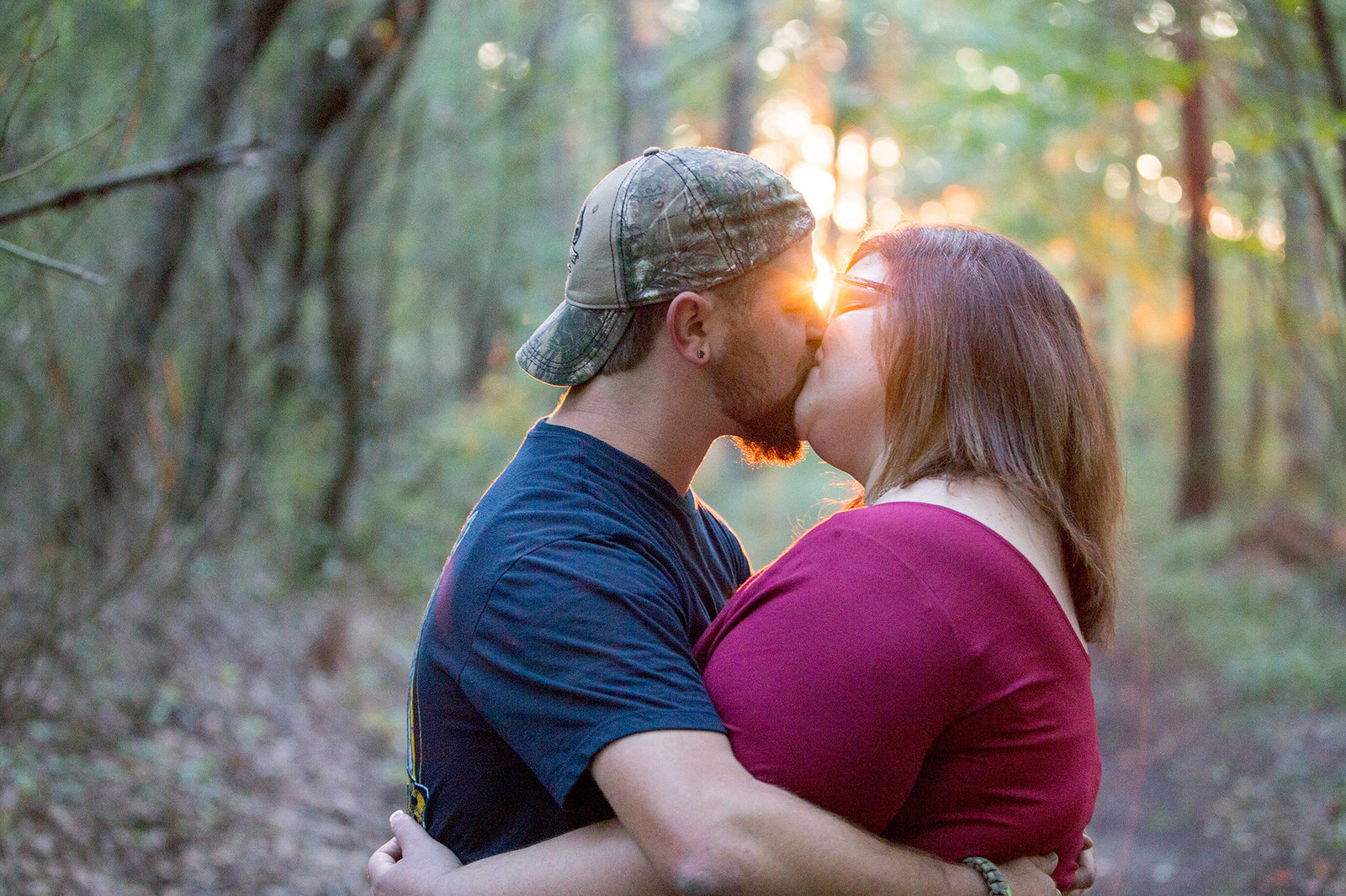engaged couple kissing on hiking trail at Presque Isle in Erie, PA