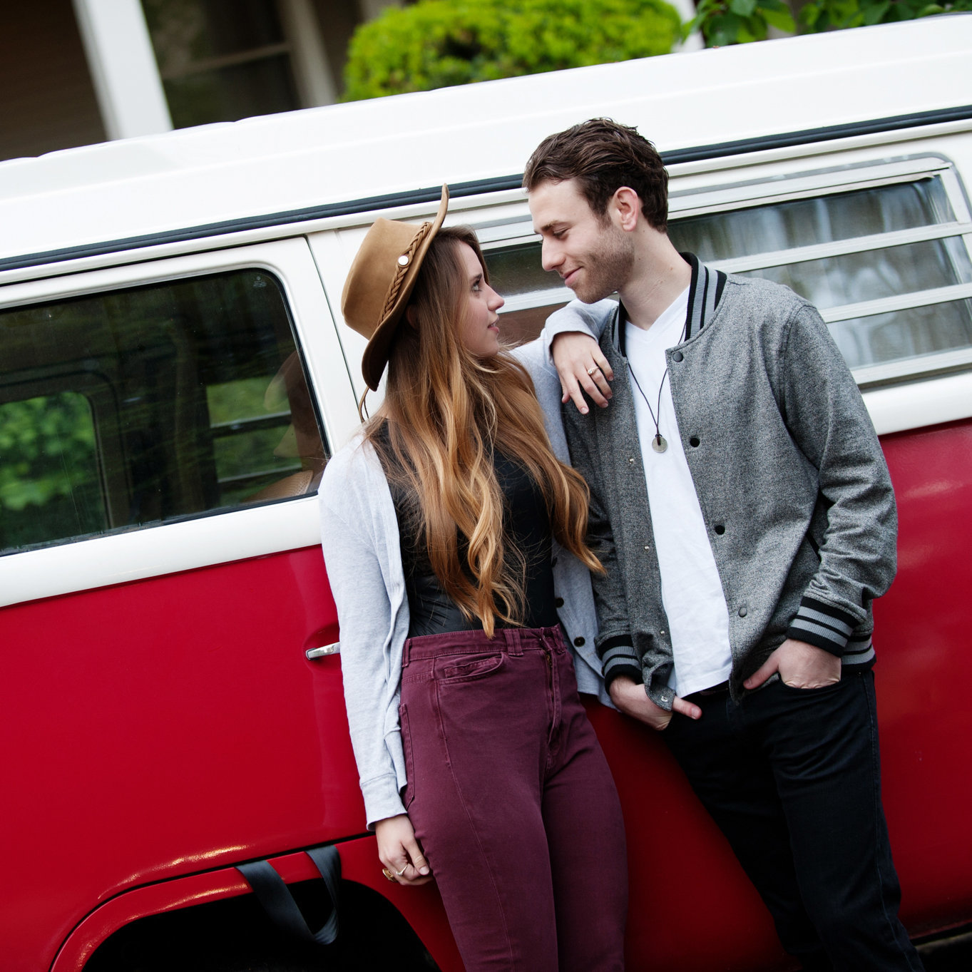 a stylish man and woman stand close in front of a vibrant red and white vw bus