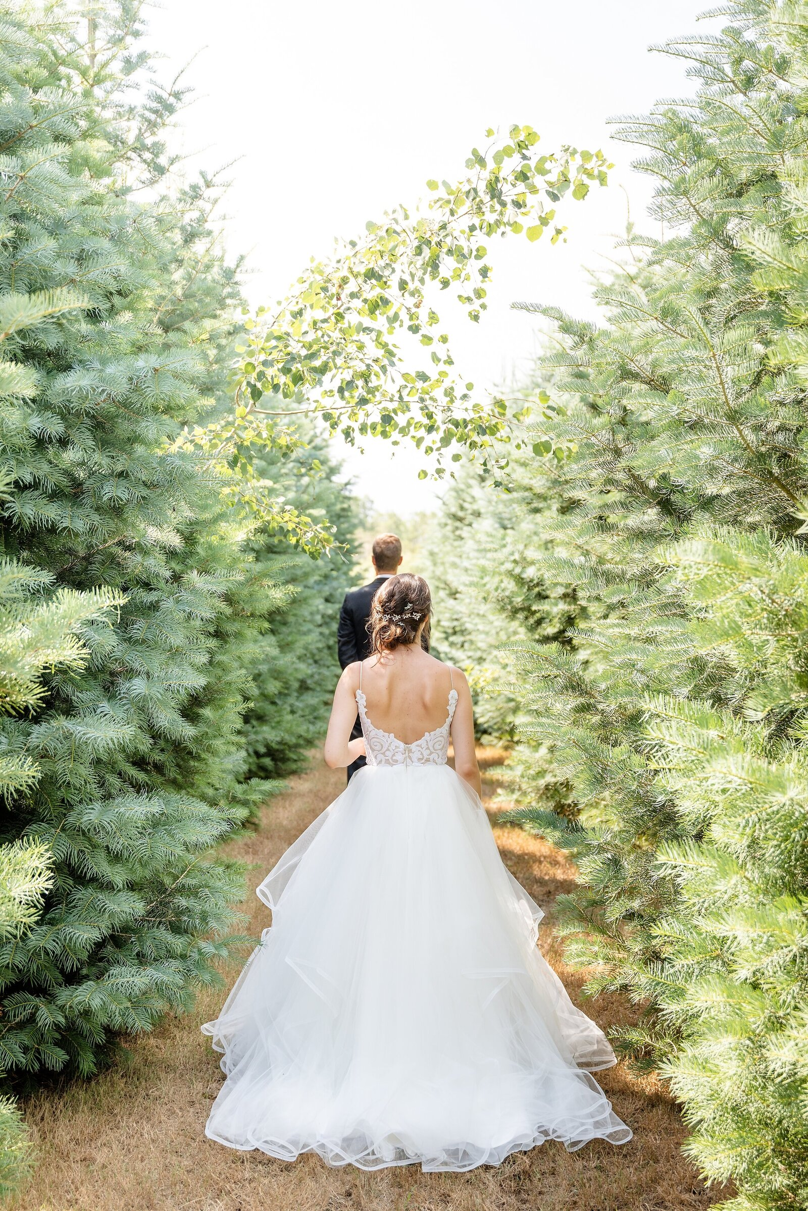 Beautiful-bride-walks-up-with-anticipation-towards-her-future-husband-with-his-back-turned-during-their-first-look-at-arrowwood-farms