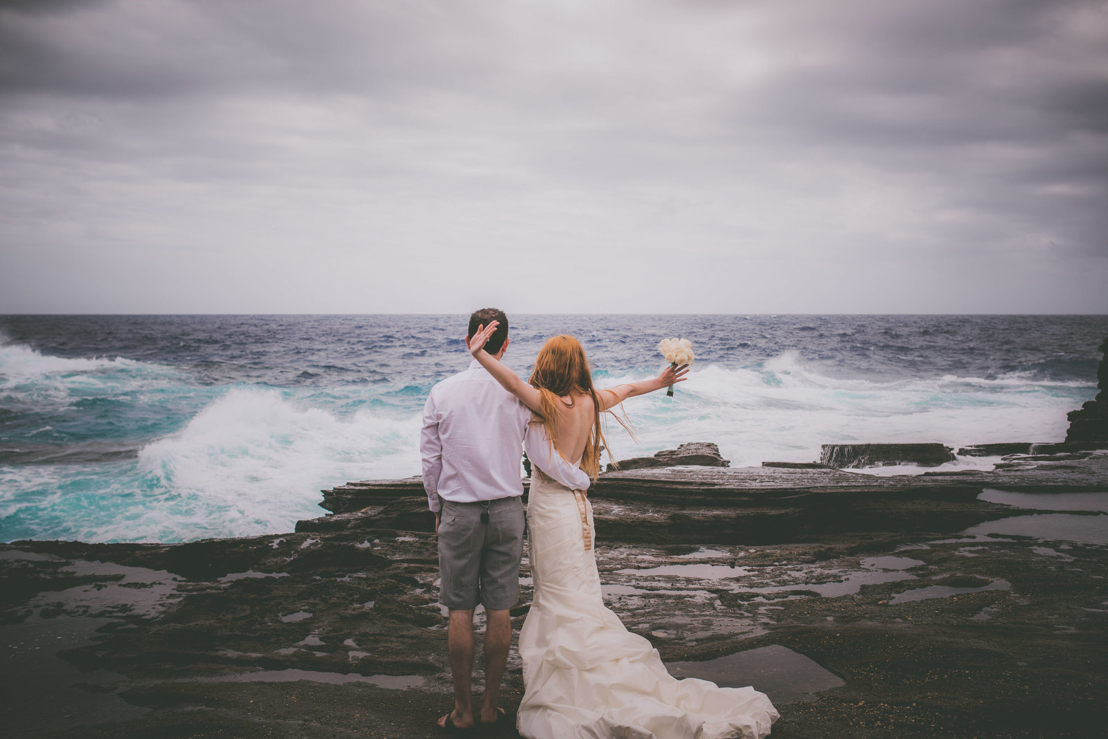 Bride raises arms when wave crashes in Hawaii.