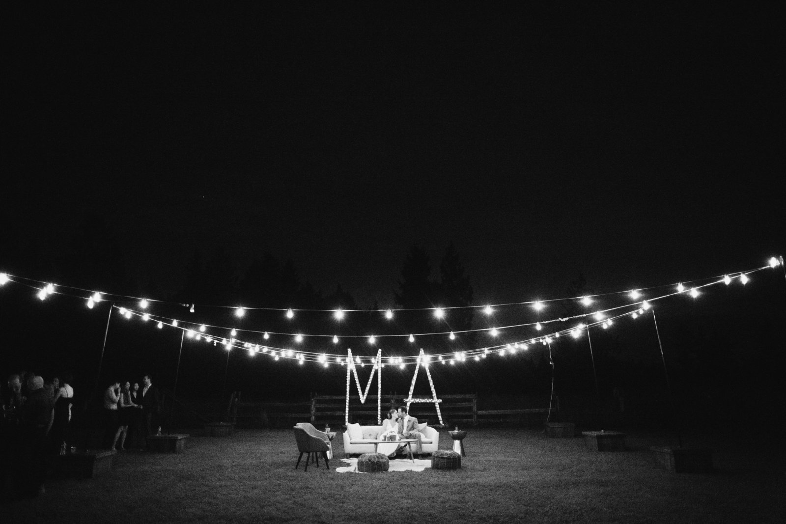 bride and groom kissing under twinkle lights in washington