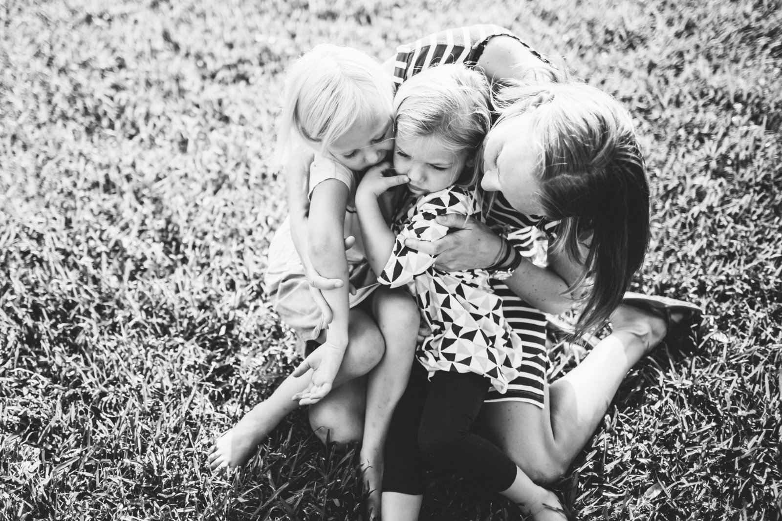 Mom hugging her two daughters in the grass in their backyard