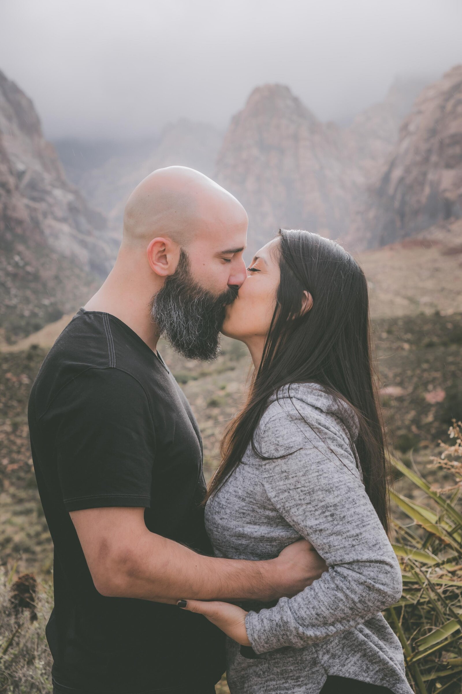 Couple kisses with mountain views behind them.