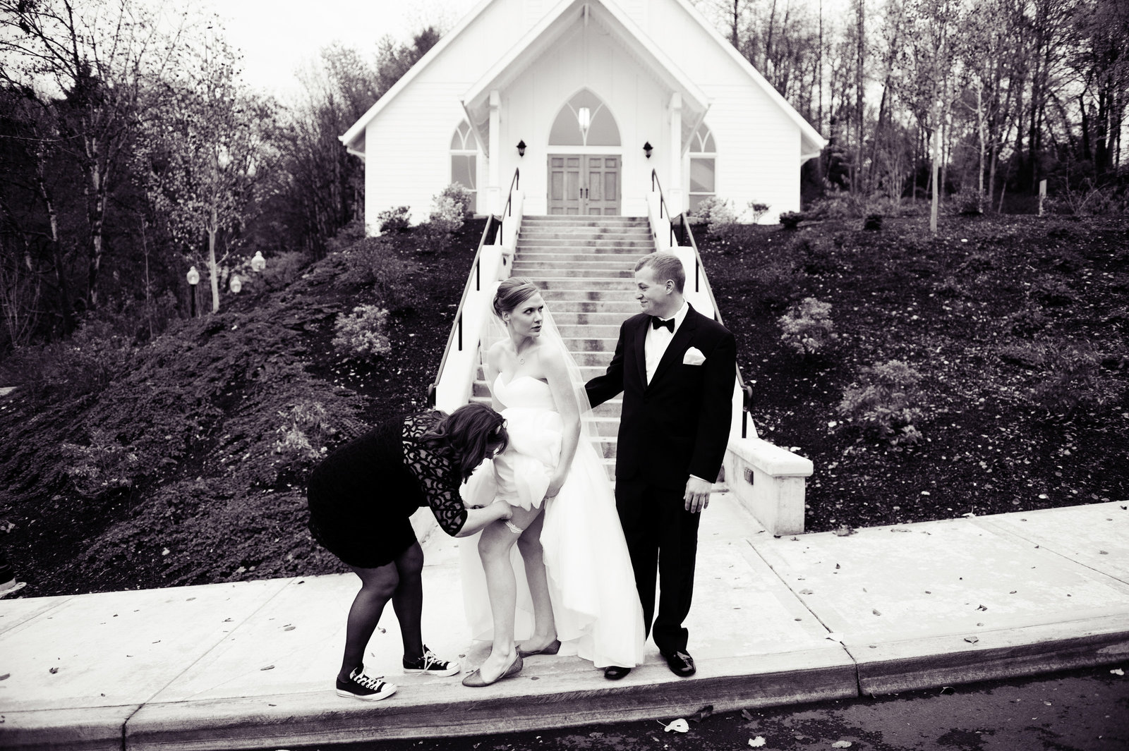 bridesmaid fixes garter in front of church as bride gives the groom a funny look