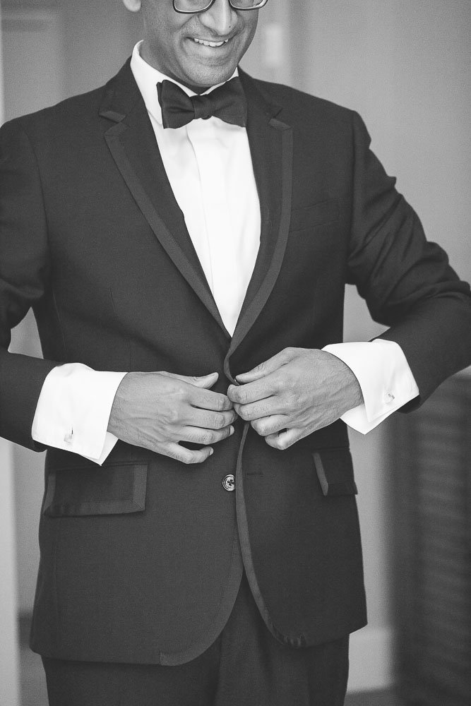 Black and Whit photo of a groom buttoning his tux jacket.