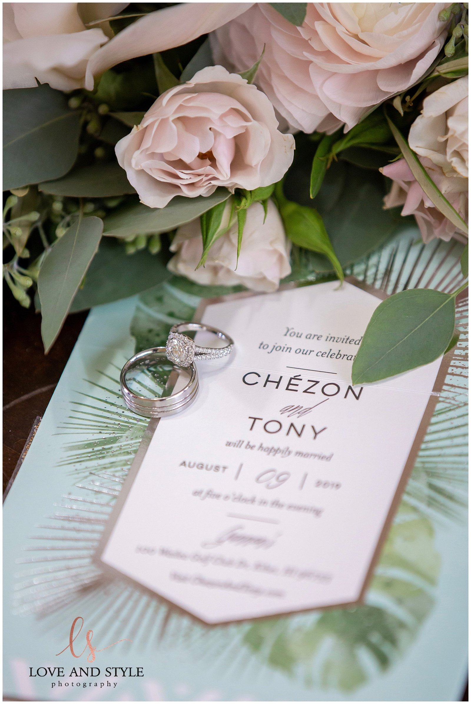 detail shot of a wedding invitation with the wedding rings