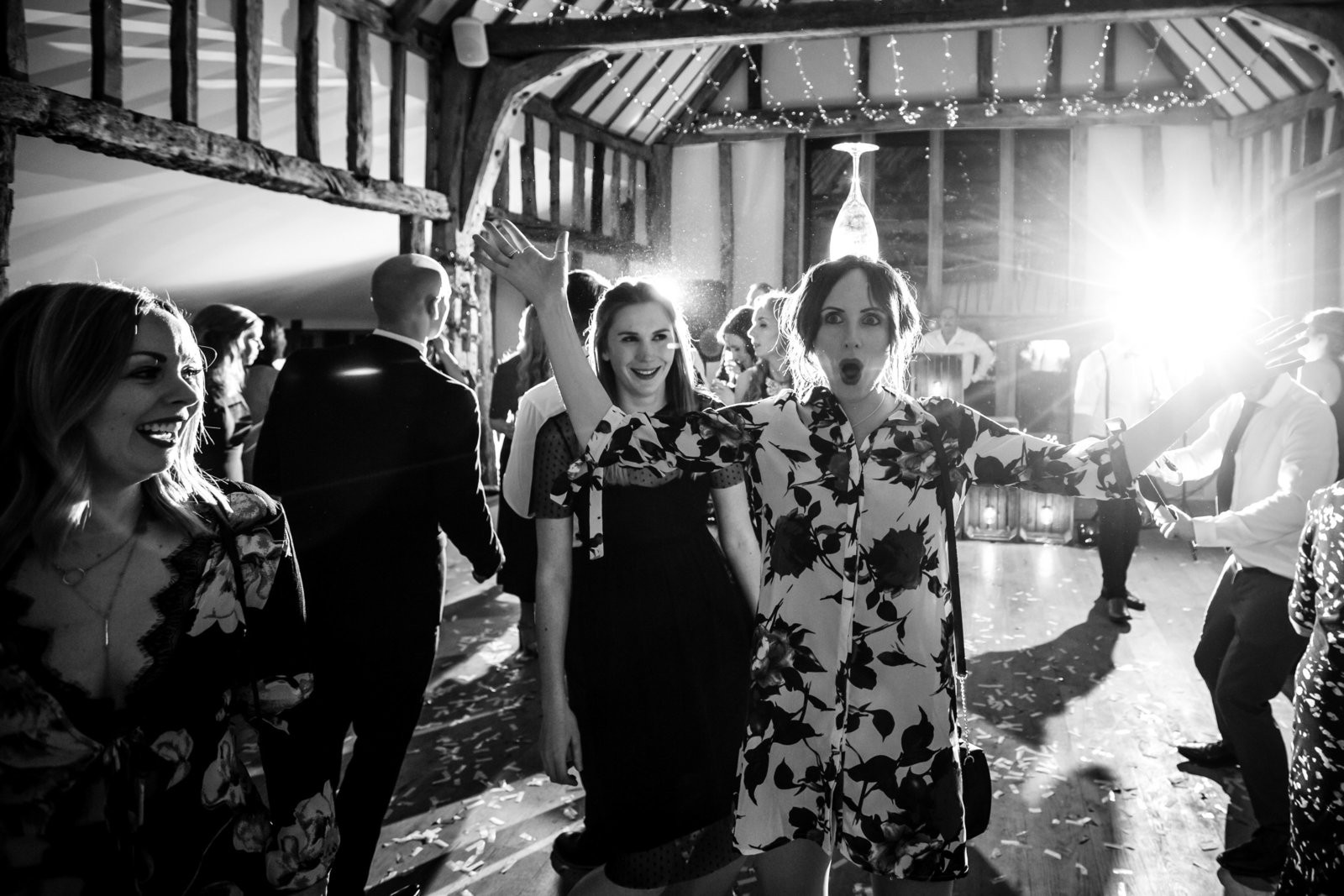 A happy lady guest balances a wine glass on her head during the dancing at a Norfolk barn wedding