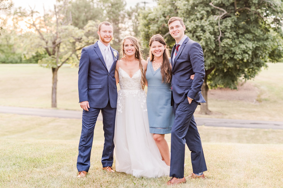wedding-couple-posing-for-a-photo-with-their-photographer