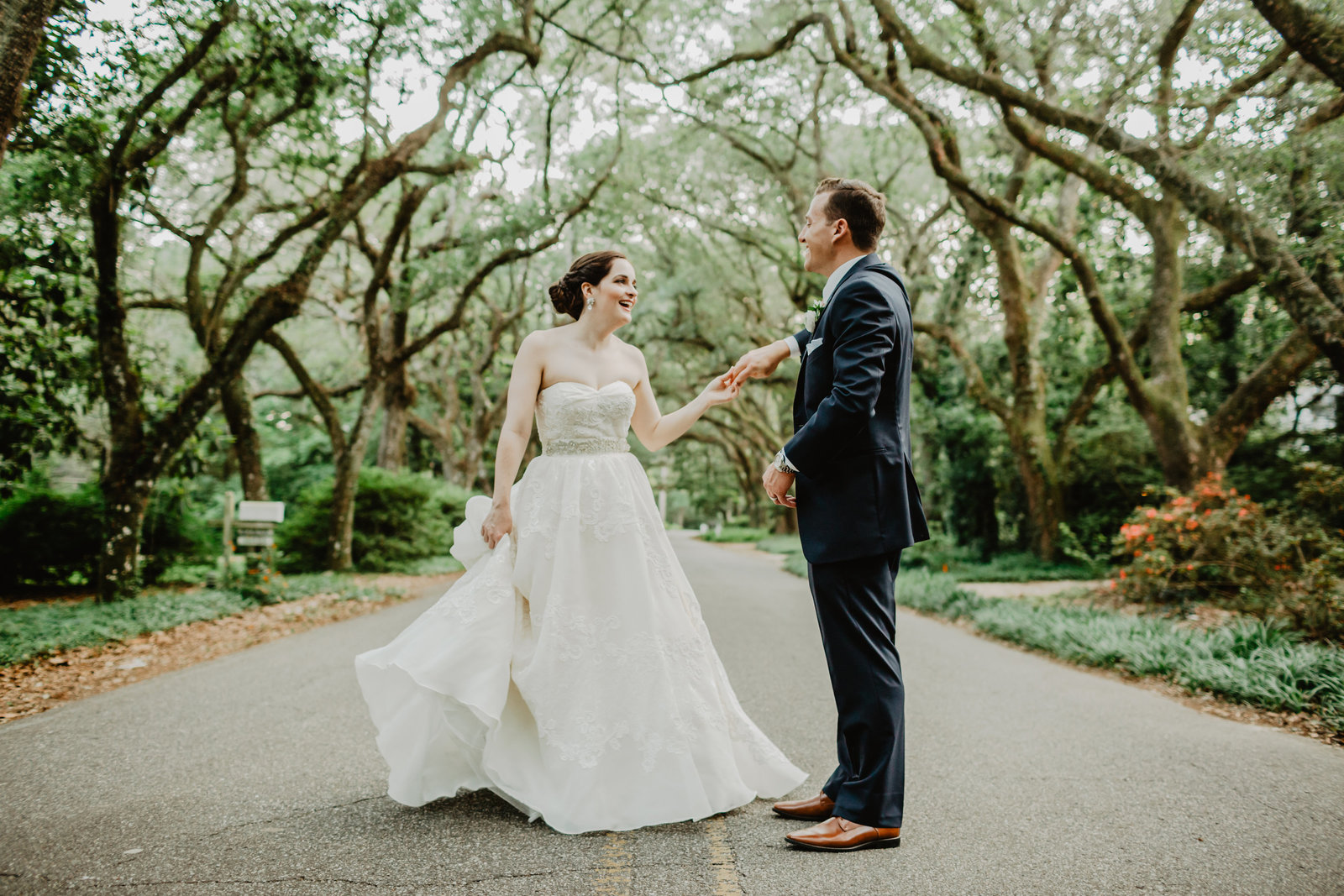 Groom spins bride on road with perfect tree wrapped street in Magnolia Springs