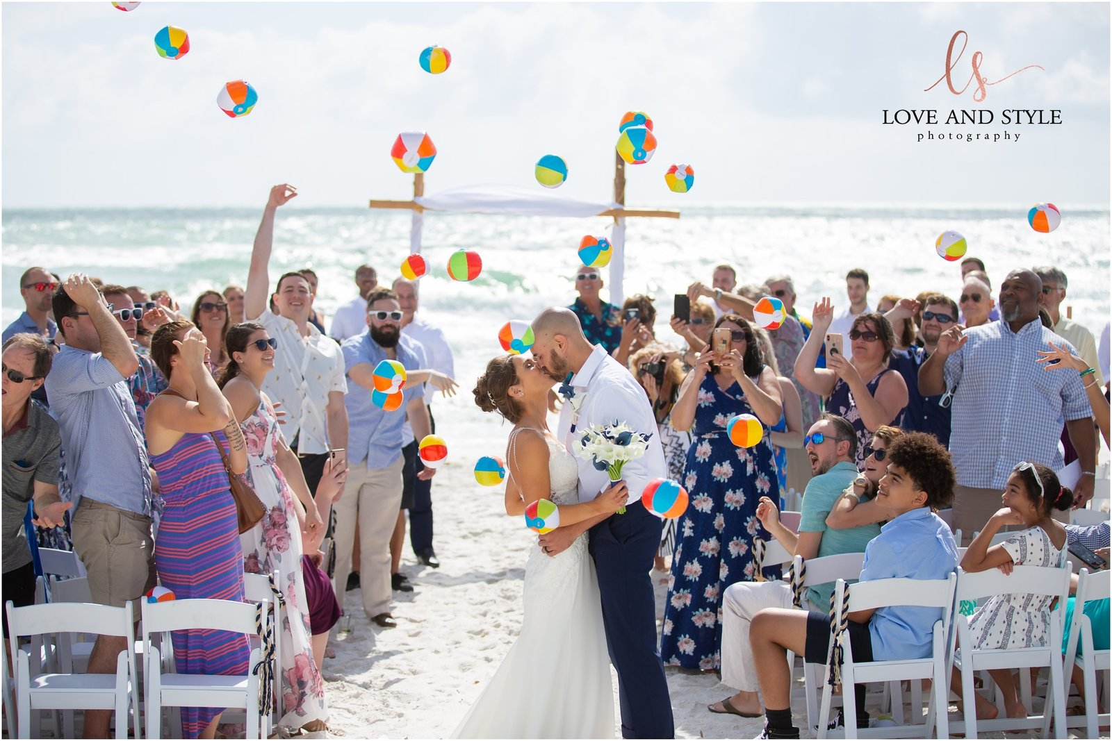 Bride and Groom kissing at the end of the aisle while guests throw beach balls in the air at The Beach House Restaurant on Anna Maria Island
