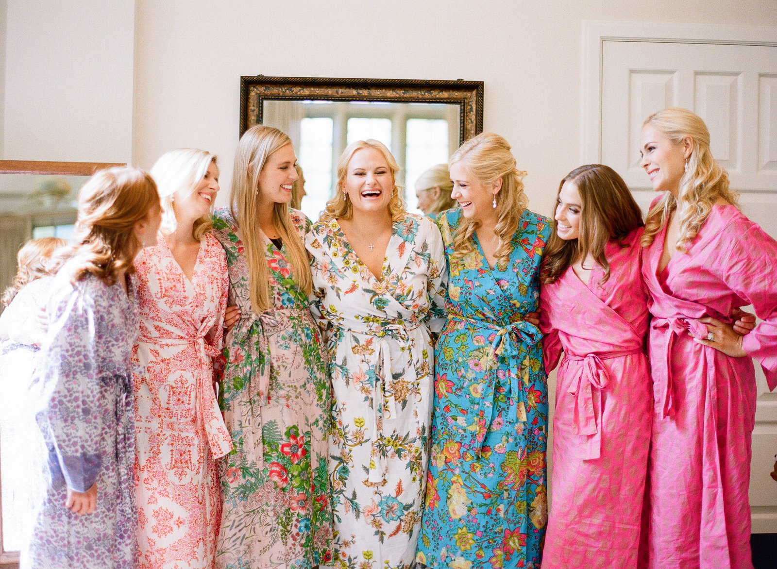 bridesmaids in colorful robes getting ready for a wedding