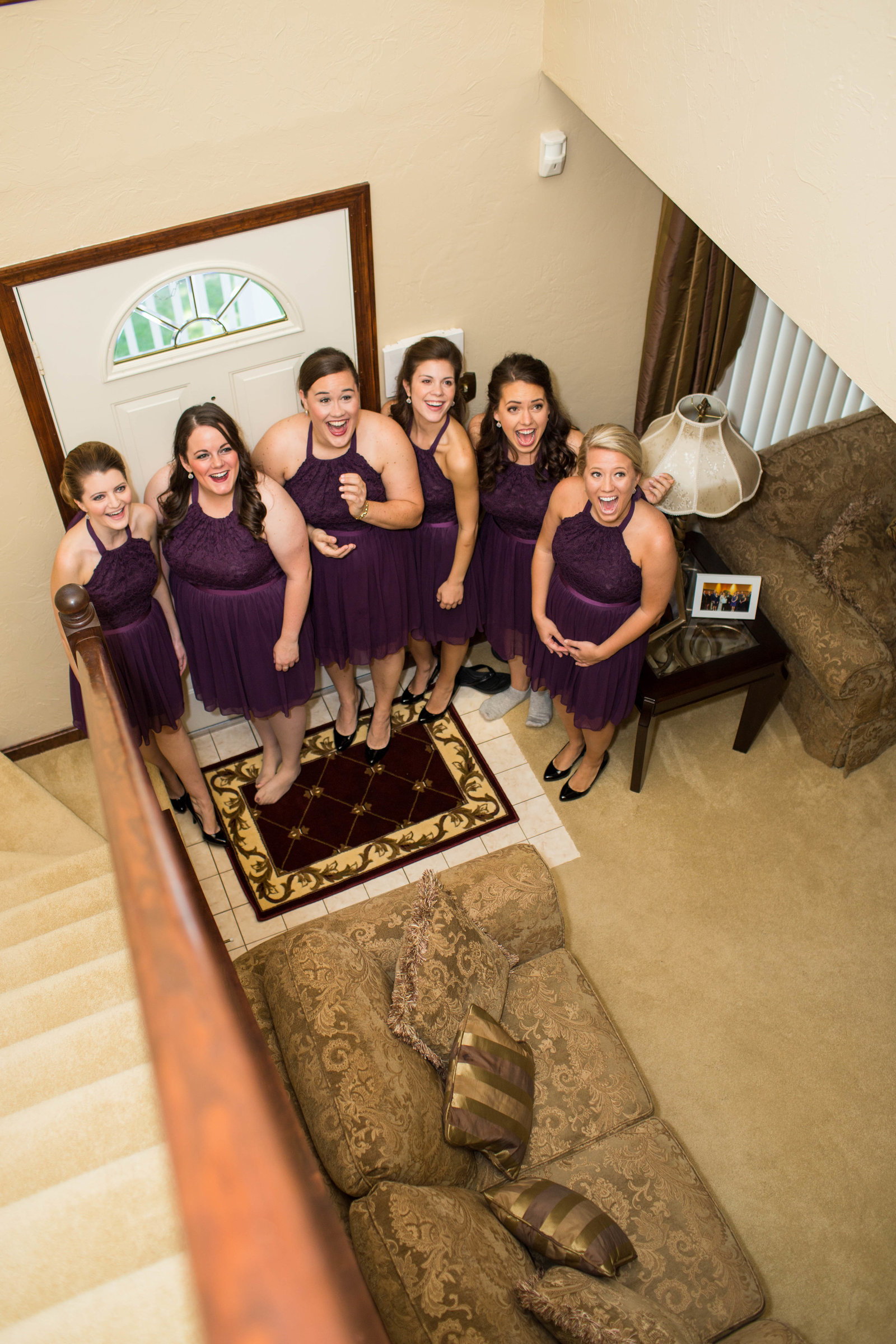 bridesmaids wait at the bottom of staircase for the bride