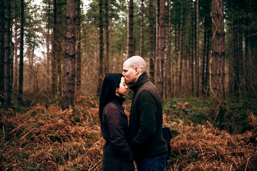 Natural photograph of relaxed couple laughing and cuddling outside under a tree in the Norwich woodland