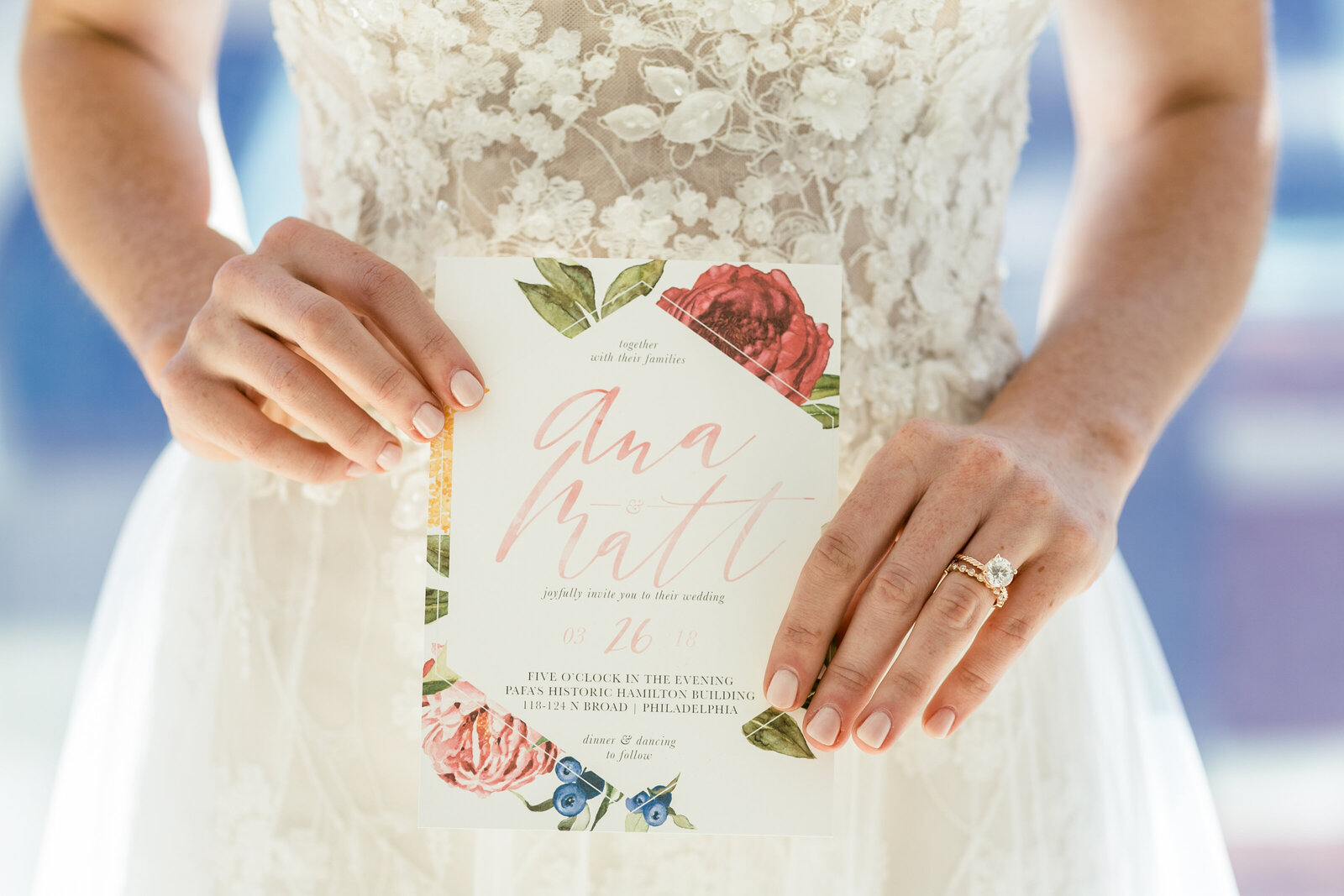 brides hands holding modern wedding invitation