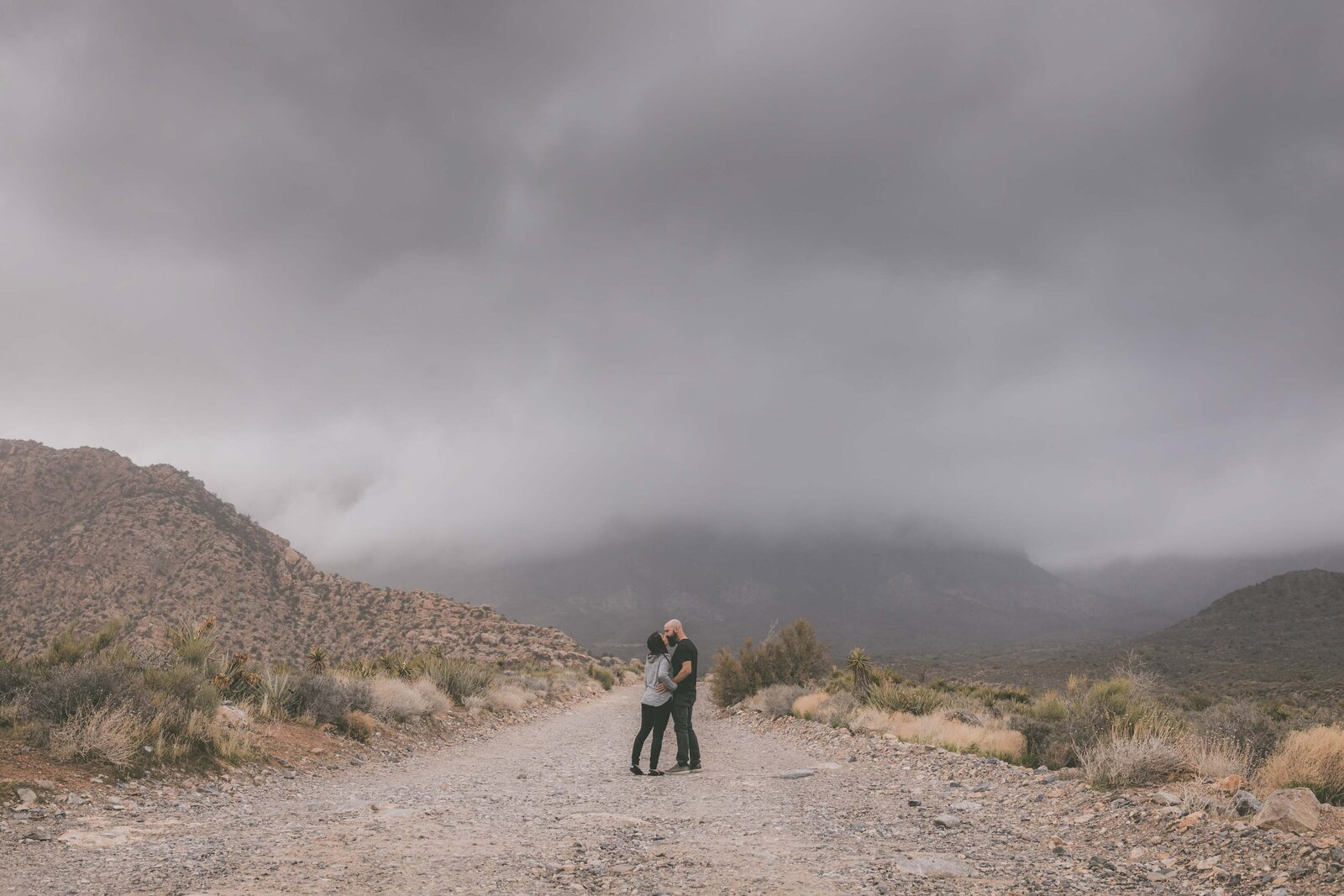 Couple pauses to kiss among desert road and stormy clouds.