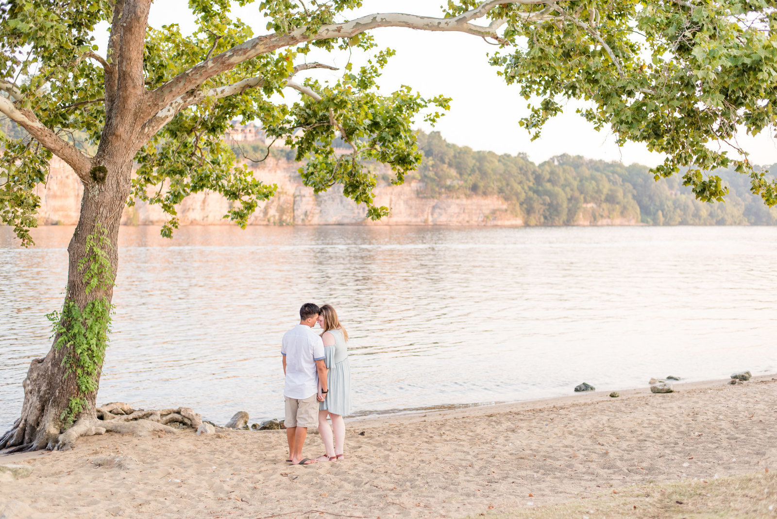 Couple stands under tree by the water.