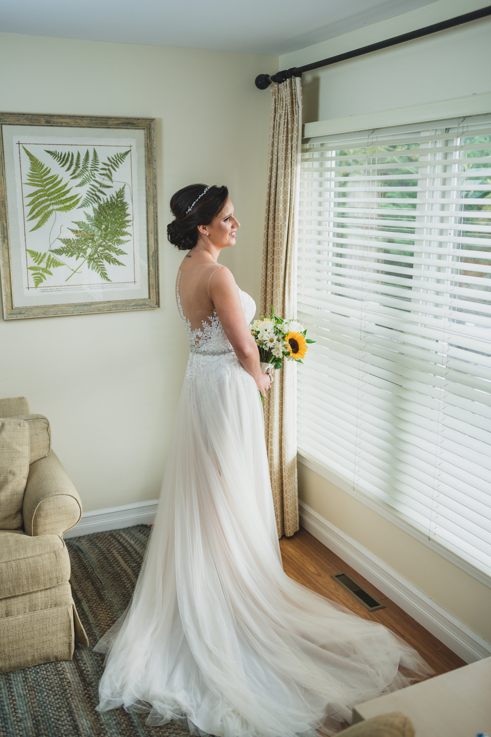 photo of bride in gown holding bouquet and looking out the window from wedding at Three Village Inn