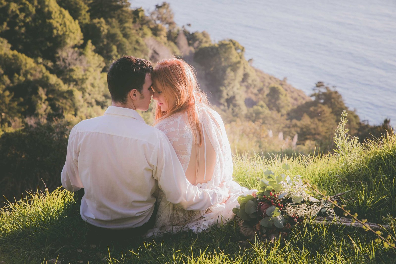 A couple touches foreheads while enjoy a cliff view on the ocean in Big Sur.