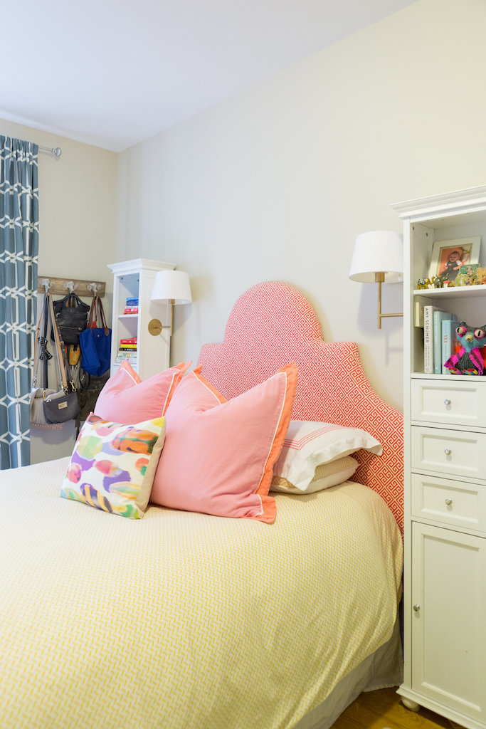 A bed with a pink and orange patterned headboard and pillows.