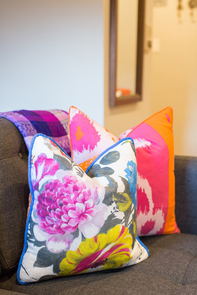 Bright and colorful throw pillows on a grey sectional.