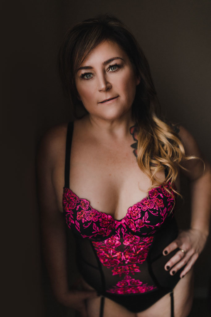 Woman in pink floral lace bodysuit posing with a hand on hip