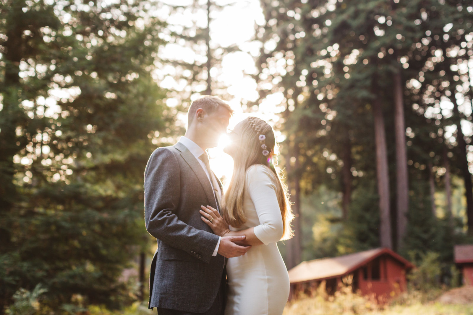 sun peeking through between mendocino wedding couple surrounded by redwoods