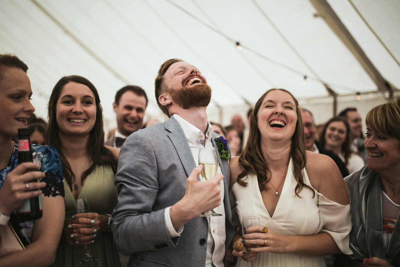 The Bride and Groom laugh hysterically whilst listening to the Bestman's speech, surrounded by their wedding guests in a marquee in a field in Norfolk.