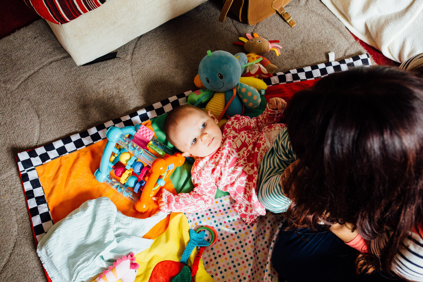 Colourful photograph of mum playing naturally with her baby at home