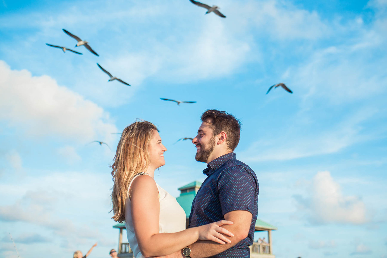 Engaged Couple has birds and blue skies above them, Folly beach in Charleston, South Carolina