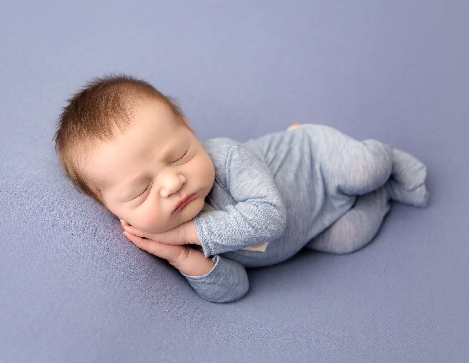 Sleeping newborn boy posed in our Rochester, Ny studio.