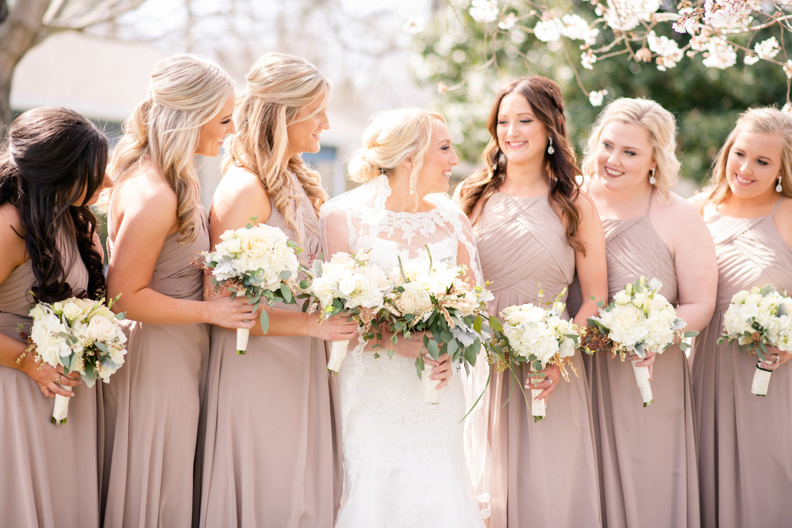 bride with bridesmaids under cherry trees
