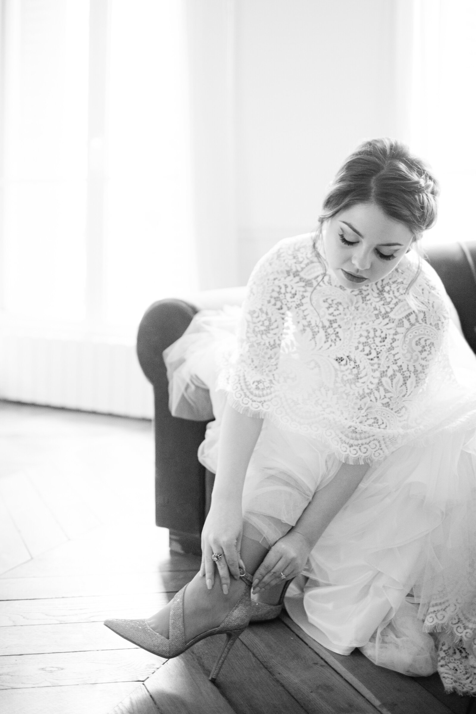black and white photos of bride putting her shoes on