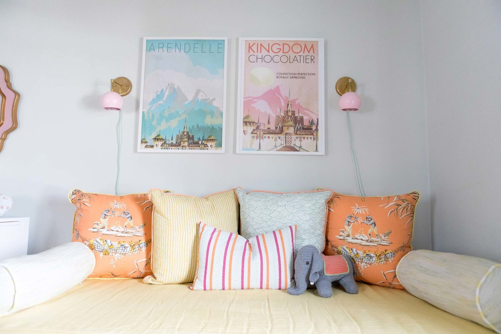 A day bed with colorful throw pillows and two framed posters.