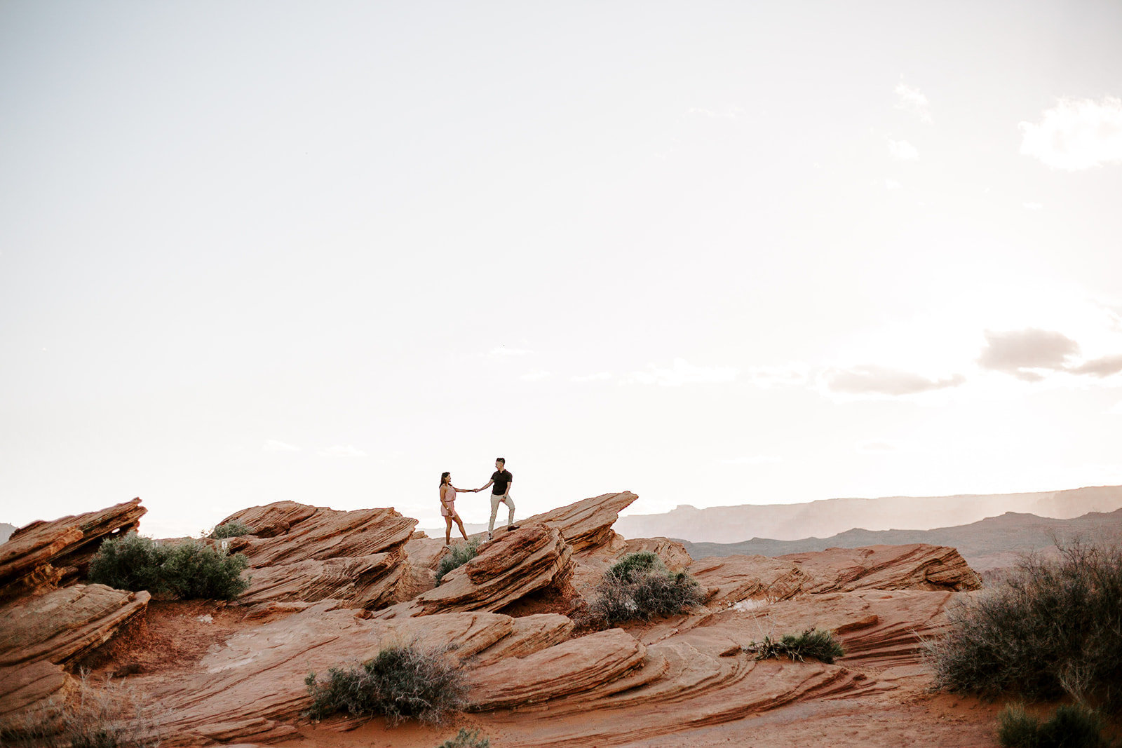 Couple holding hands standing on a red rock during their Arizona Engagement Session