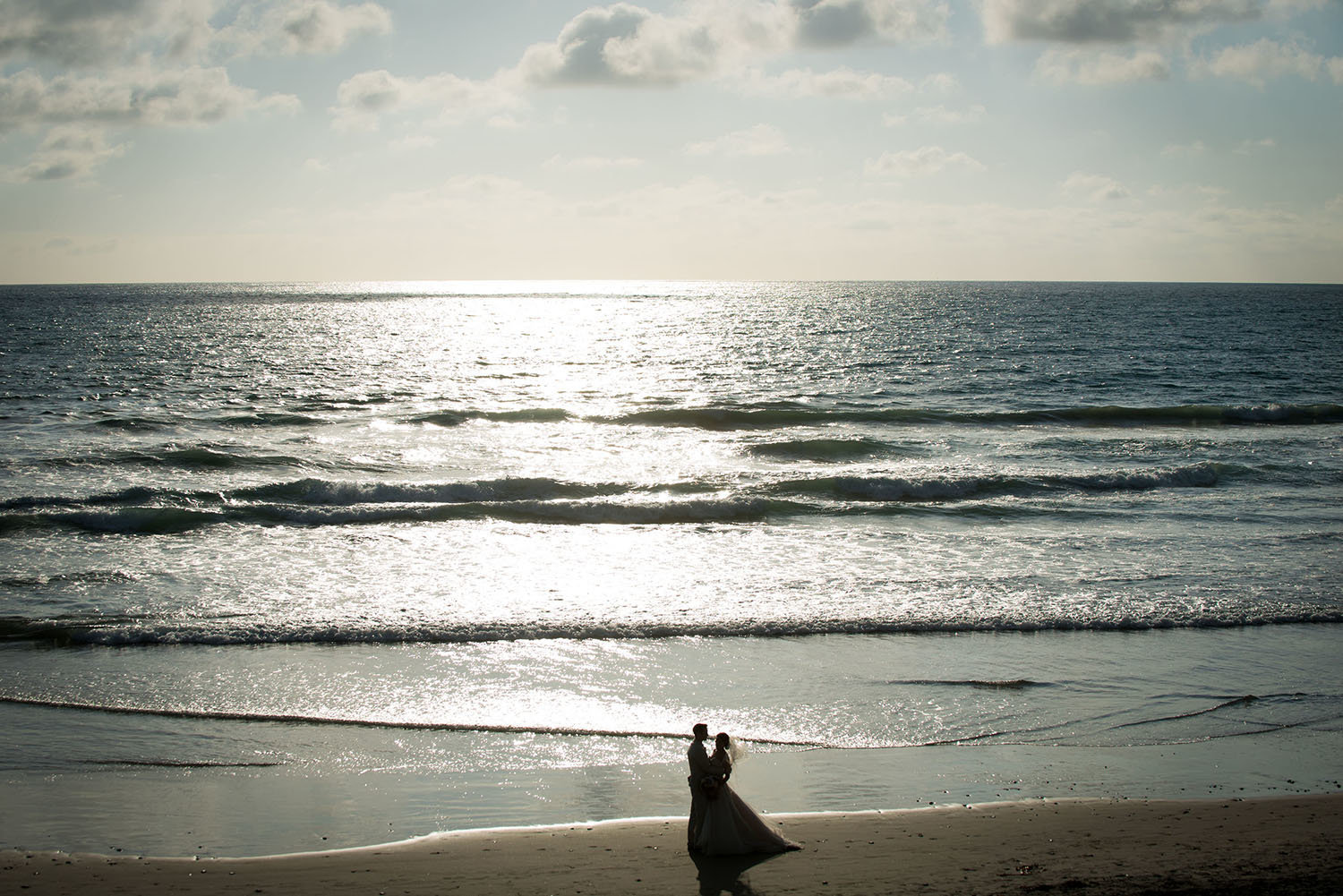 Creative silhouette of the bride and groom on the beach in Del Mar