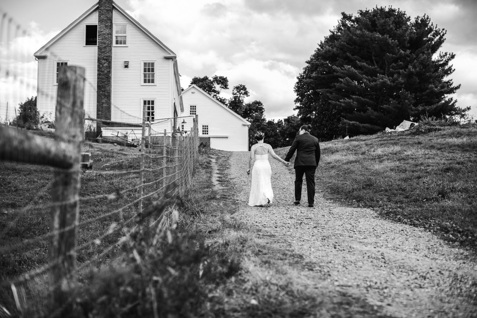 black and white image of bride and groom walking down farm path in ma