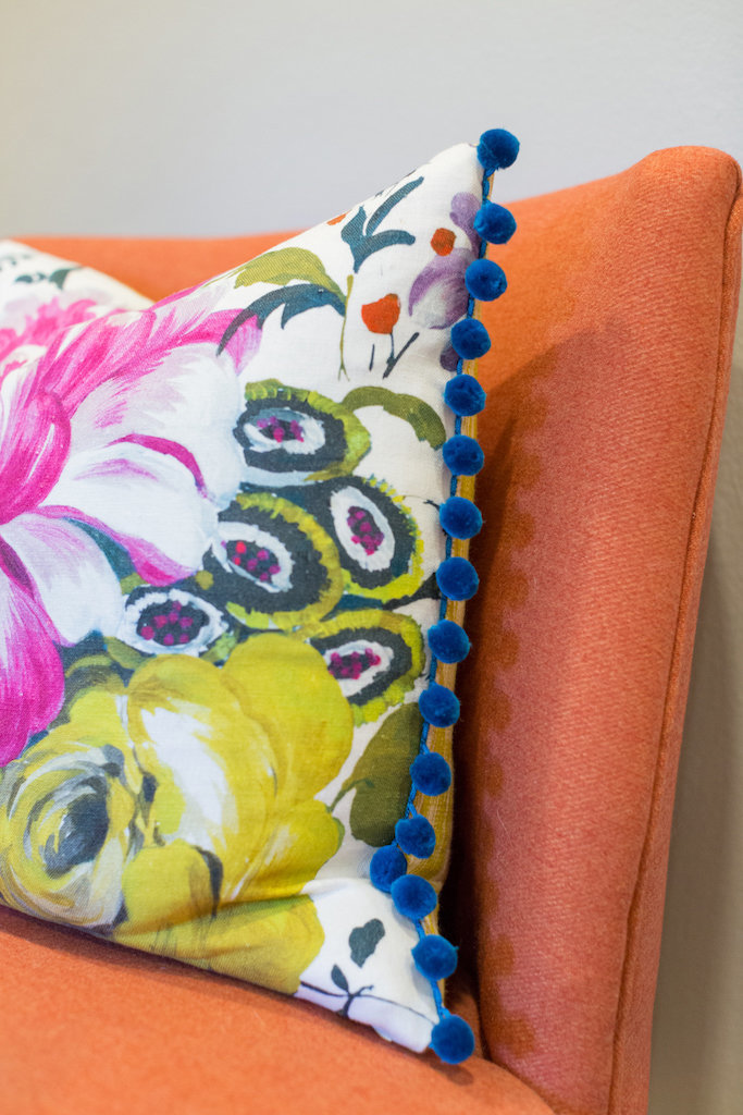 An orange chair with colorful floral throw pillow.