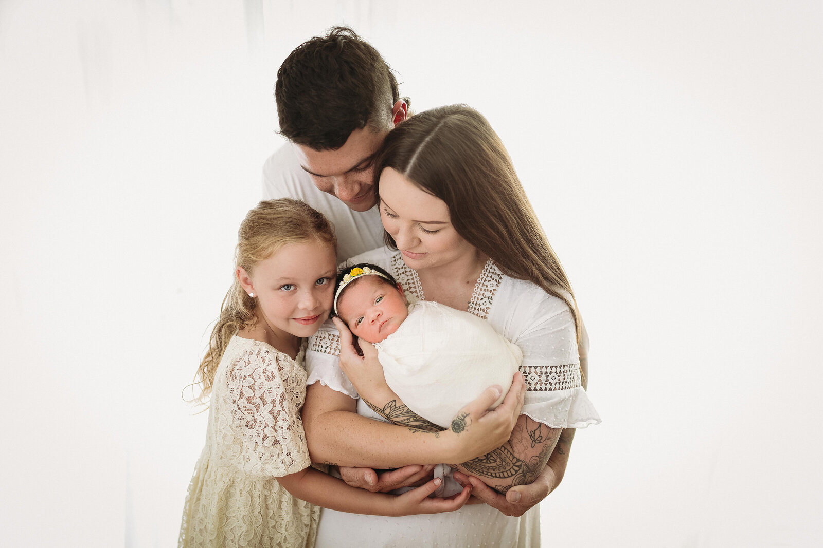 In-studio portrait of family holding newborn baby