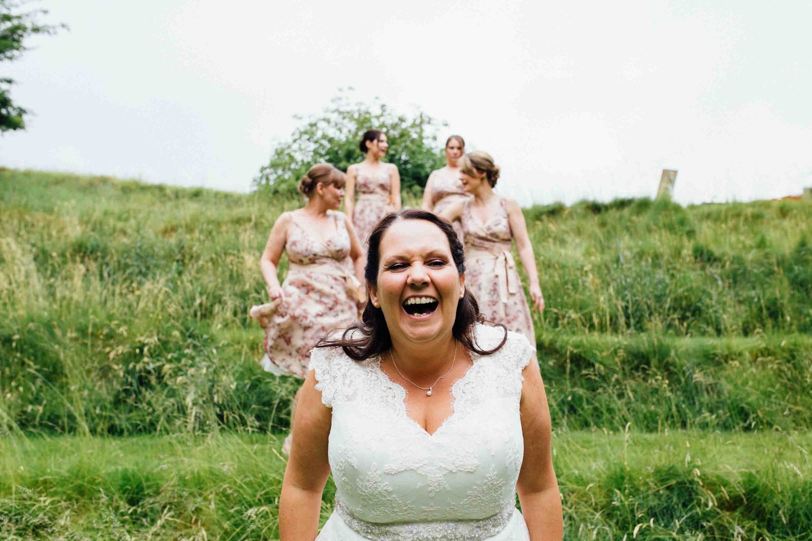 Laughing bride with pink bridesmaids on a grassy hill at The Keeper and The Dell, Norwich, Norfolk
