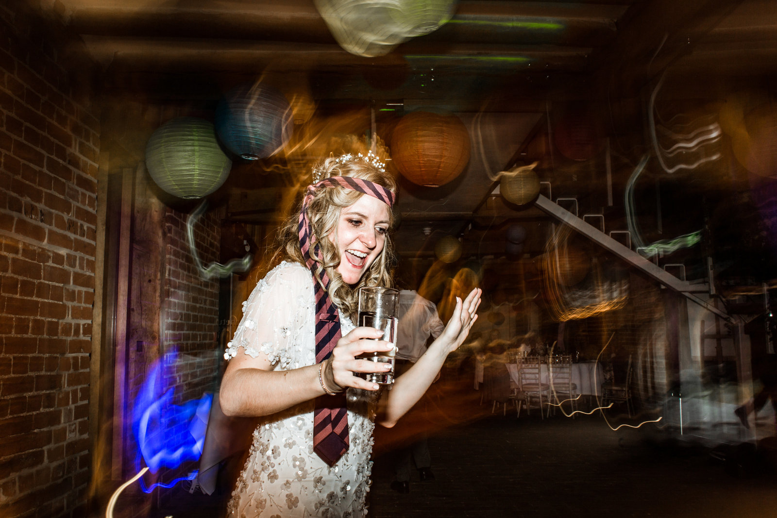 Slightly tipsy Bride dancing on the dance floor with a suit tie wrapped around her head and a beer in her hand at a barn wedding venue in Norfolk.