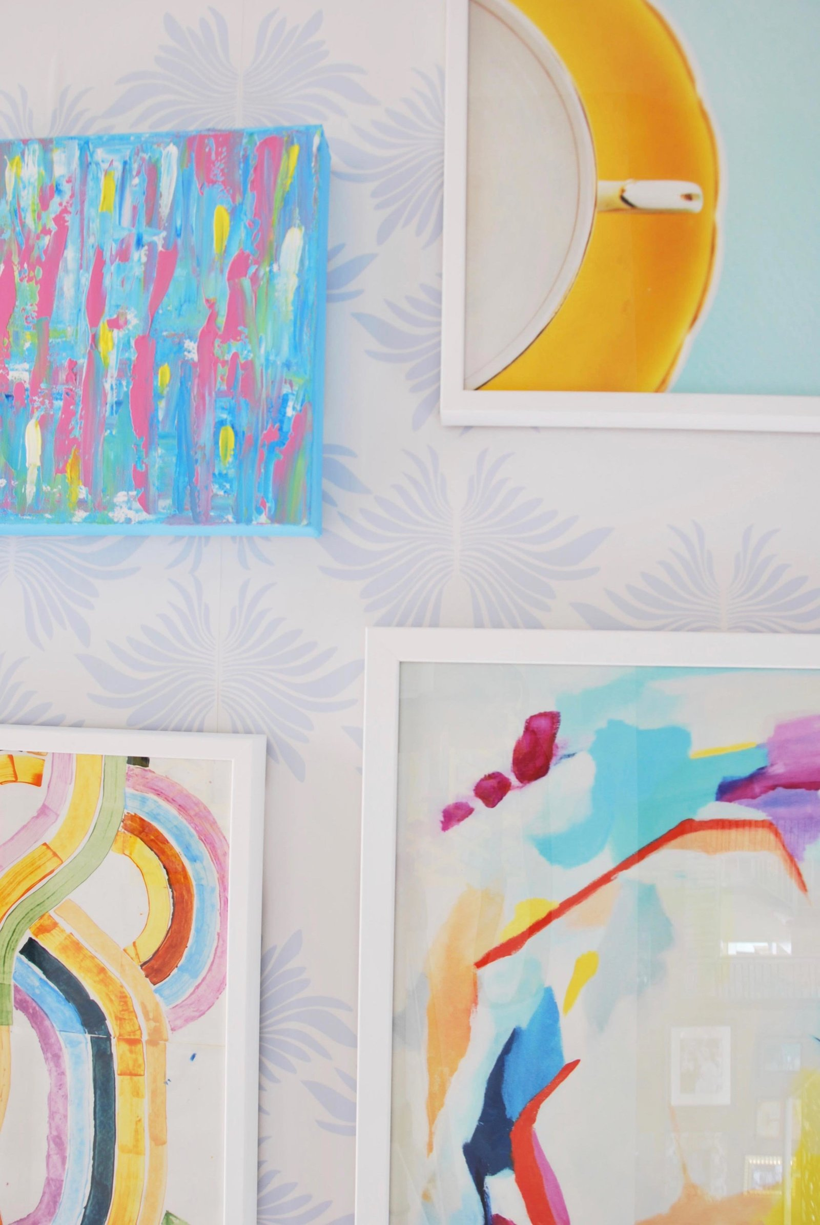 A colorful gallery wall of paintings in white frames.