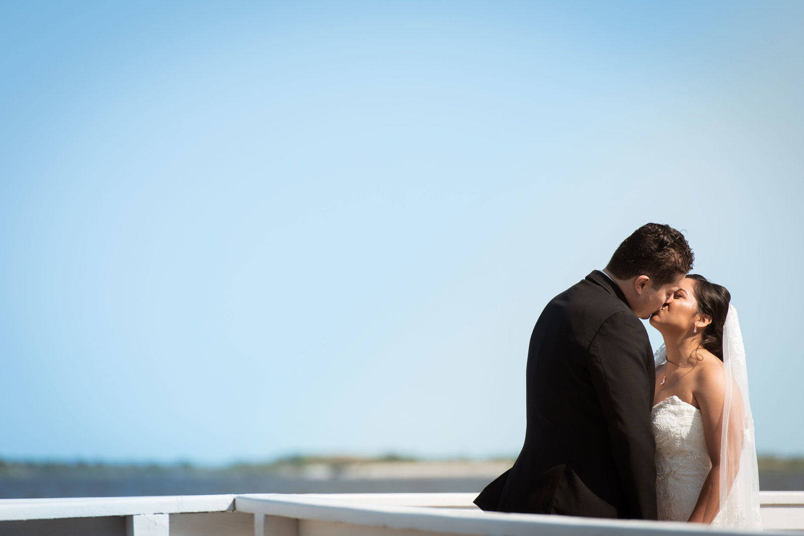 Bride and groom kissing on the dock at Chateau La Mer