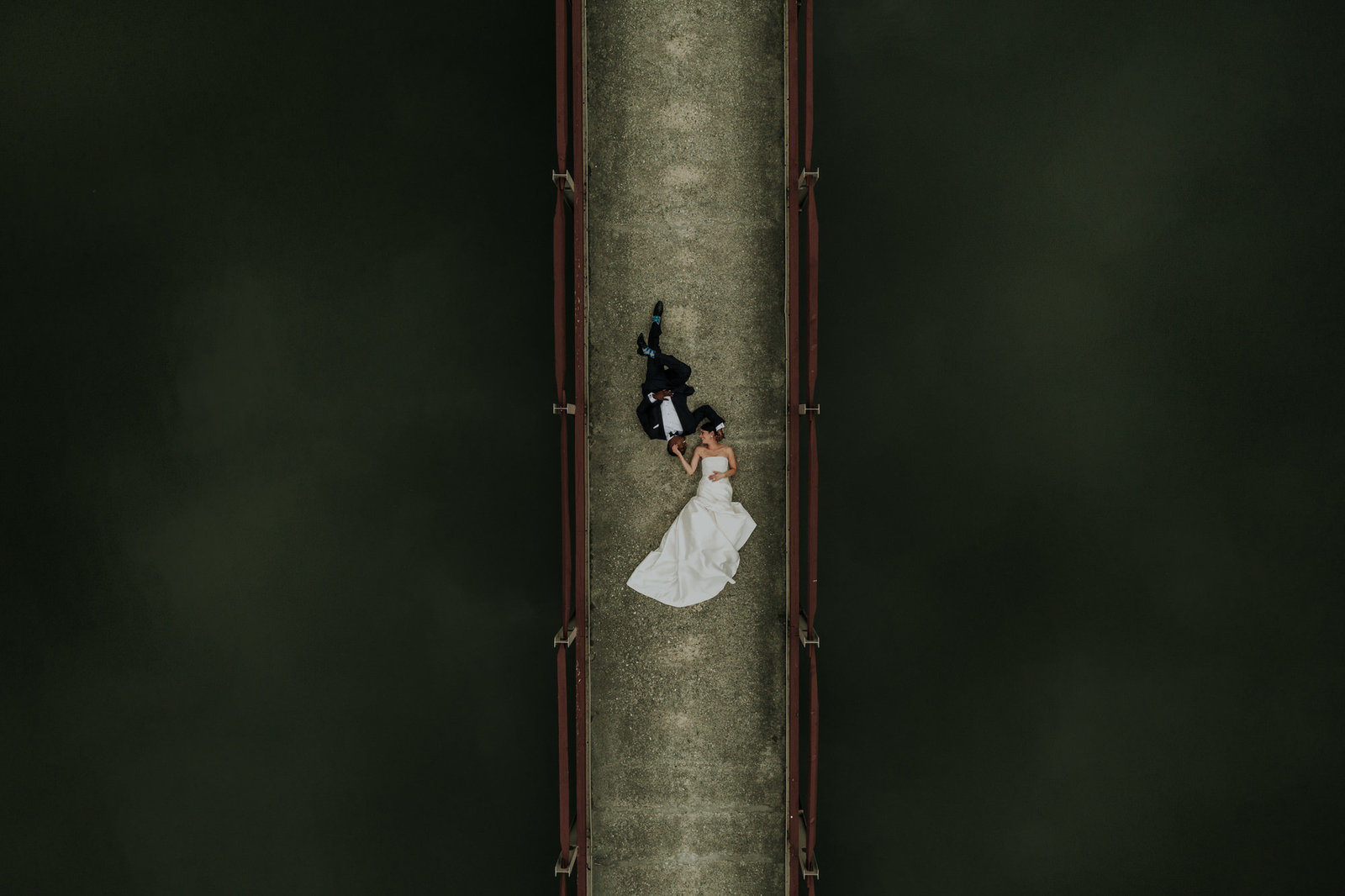 overhead drone photo of a couple laying on a bridge